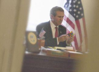 O então presidente dos EUA, George Bush, diverte-se com um cubo de Rubik, 2005 - ALISON JACKSON